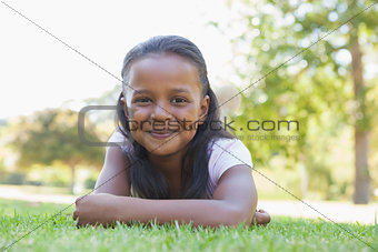Little girl lying in the park smiling at camera