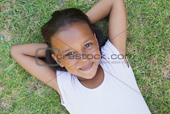 Little girl lying on the grass smiling at camera