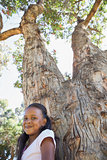 Little girl sitting by large tree smiling at camera