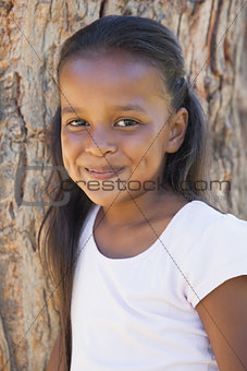 Little girl by large tree smiling at camera
