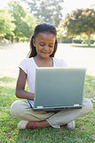 Little girl sitting on grass using laptop