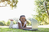 Little girl lying on grass using laptop smiling at camera