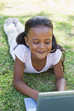 Little girl lying on grass using laptop