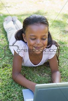 Little girl lying on grass using laptop