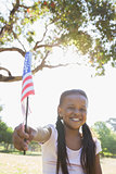Little girl sitting on grass waving american flag