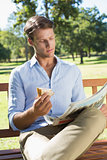 Handsome man sitting on park bench eating sandwich and reading paper