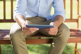 Man sitting on park bench using tablet
