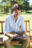 Smiling man sitting on park bench using tablet