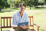 Smiling man sitting on park bench using tablet looking at camera