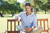 Smiling man sitting on park bench using tablet drinking coffee
