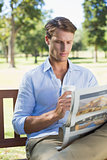 Man sitting on park bench drinking coffee and reading paper