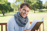 Stylish young man holding journal smiling at camera