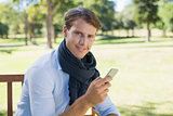 Stylish young man sitting on park bench sending a text