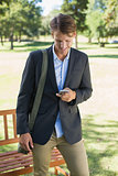Casual businessman texting on smartphone in park