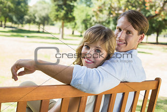 Couple relaxing on park bench together smiling at camera