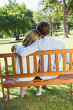 Couple relaxing on park bench together
