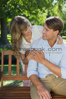 Affectionate couple relaxing on park bench together