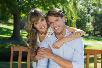 Affectionate couple relaxing on park bench together smiling at camera