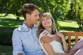 Affectionate couple relaxing on park bench together smiling at each other
