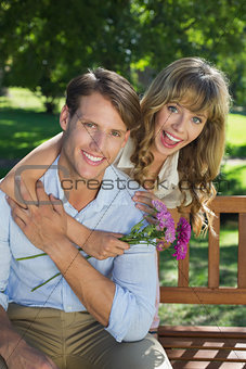 Cute couple smiling at camera in the park with girl holding flowers