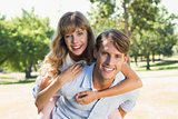 Man giving his pretty girlfriend a piggy back in the park smiling at camera