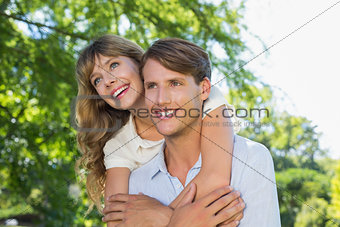 Man giving his pretty girlfriend a piggy back in the park smiling