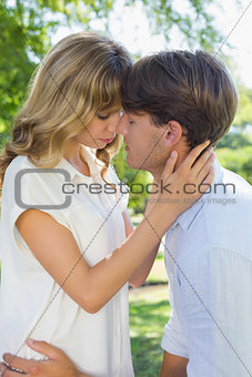 Cute couple hugging and kissing in the park