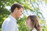 Attractive couple smiling at each other in the park