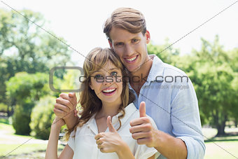 Attractive couple smiling at camera and showing thumbs up in the park