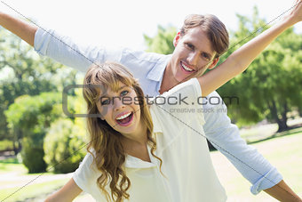 Attractive couple smiling at camera and spreading arms in the park