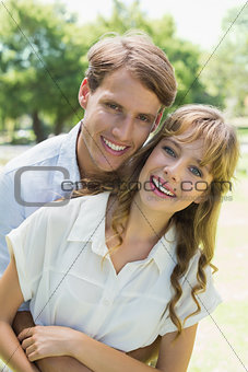 Attractive couple embracing and smiling at camera in park