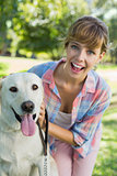Pretty smiling blonde posing with her labrador in the park