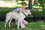 Pretty smiling blonde kneeling with her labrador in the park