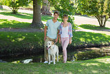 Happy couple standing with their labrador in the park smiling at camera