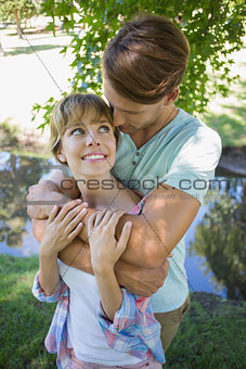 Affectionate young couple standing together in the park smiling at each other