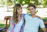 Cute couple sitting on bench in the park smiling at camera