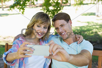 Smiling couple sitting on bench in the park taking a selfie