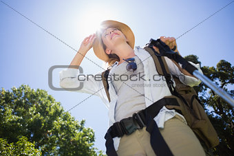Fit woman standing with hiking pole in park