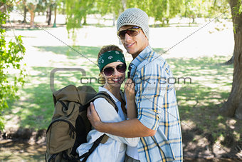 Active cute couple embracing each other on a hike smiling at camera