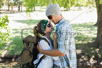 Active cute couple embracing each other on a hike smiling at each other
