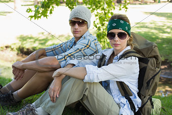 Active couple sitting down on a hike looking at camera