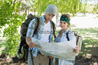 Active smiling couple sitting down on a hike holding map