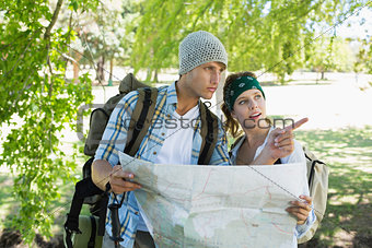 Active couple on a hike consulting the map