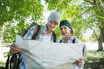 Active smiling couple on a hike consulting the map