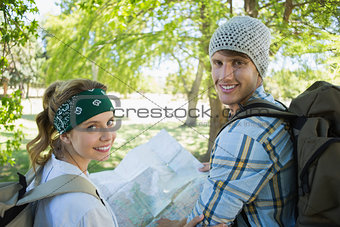 Active couple on a hike consulting the map smiling at camera