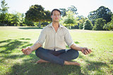 Stylish man meditating in the park