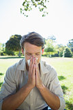 Stylish man blowing his nose in the park
