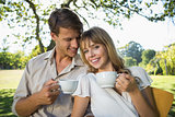 Smiling couple having tea outside in a cafe