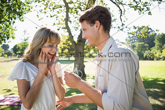 Man surprising his girlfriend with a proposal in the park