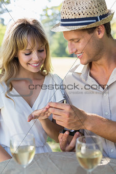 Man placing engagement ring on fiancees finger